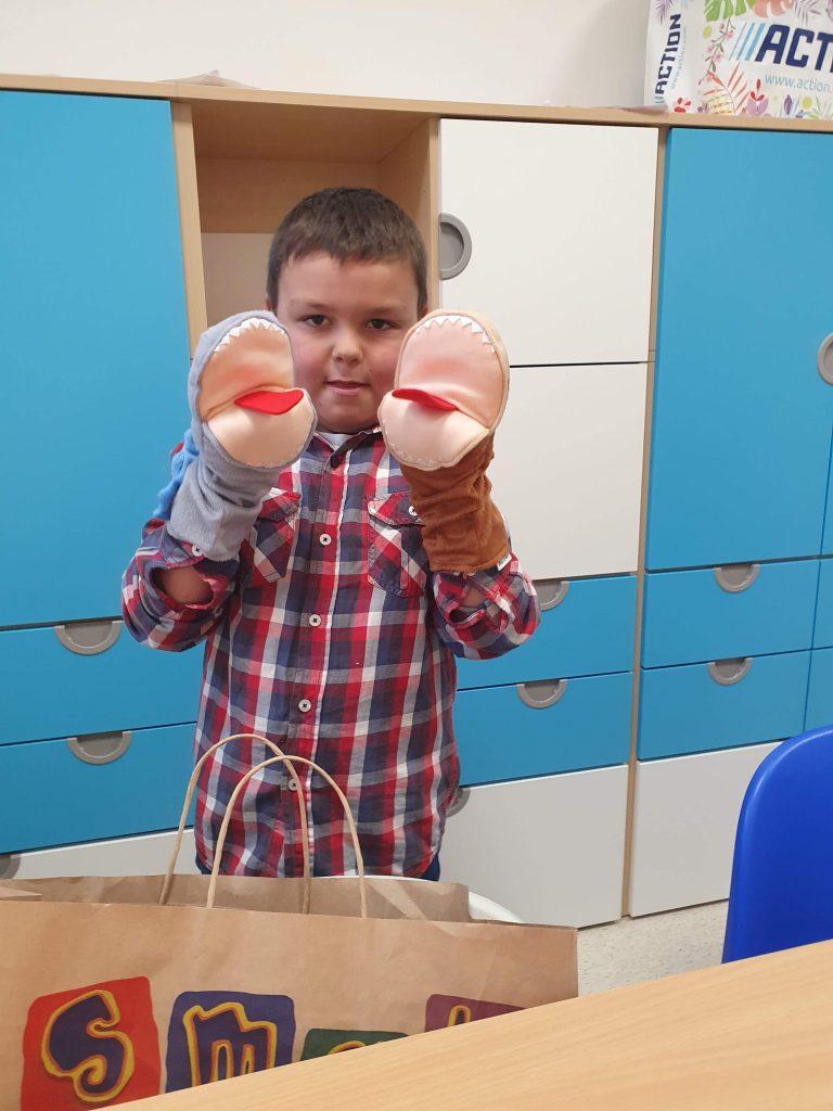chłopiec z ubranymi maskotkami na rękach
