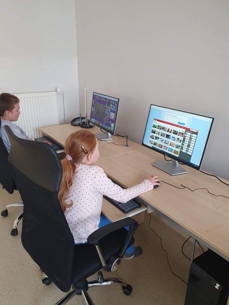 dwójka dzieci siedząca przy komputerach