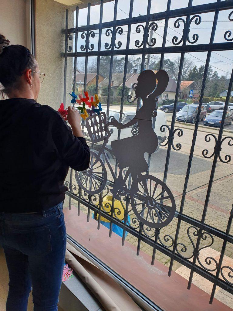 kobieta malująca na oknie